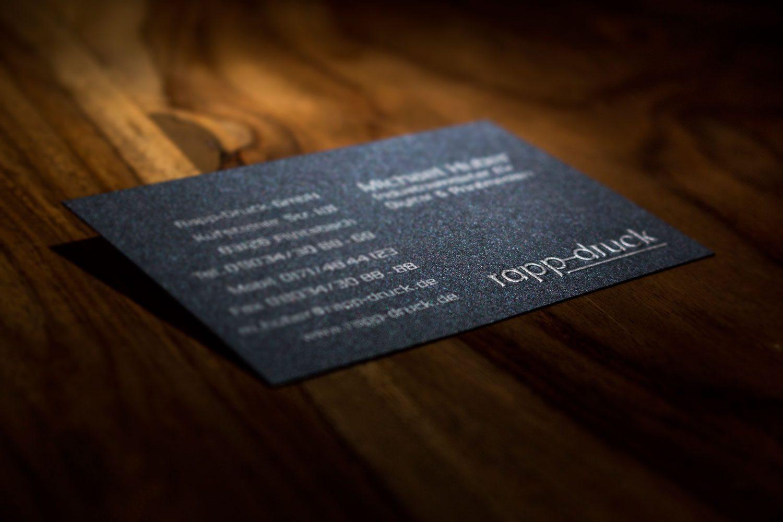 1/0-farbig silber bedruckte Visitenkarte auf 285 g/m² Stardream anthracite Papier mit Hochprägung des Rapp-Druck Logos